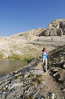 Woman hiking along lake Conturines, La Varella, Naturpark Fanes_Sennes_Prags, Dolomites, Trentino_Alto Adige/South Tyrol, Italy