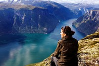 Young woman looking at the Aurlandsfjord, Prest, Aurland, Sogn og Fjordane, Norway, Scandinavia, Europe