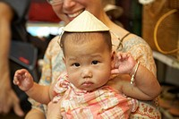 Baby girl wearing Asian hat