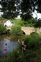Children bathing in river near old stone bridge, Lauterecken, Rhineland_Palatinate, Germany