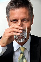 Businessman drinking water from glass, portrait