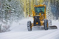 Grader plowing snow from the road surface on a winter day on a back country road in Alberta, Canada.
