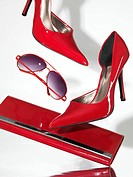 Stylish red high heel stiletto shoes sunglasses and a clutch hand bag falling on metal surface with white background behind