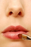 Close_up of woman applying lipstick