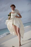 bride running happily on the lonely beach