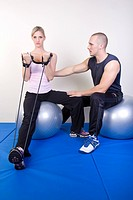 young woman doing fitness exercise on Swiss ball, instructed by trainer