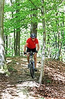 sporty senior with mountain bike in the woods