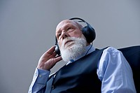 Businessman wearing headphones and listening to music