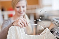 Young woman taking a top from a clothes rack