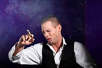 Man holding a cigar and coughing