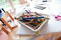 Coloured pencils in a basket on a table, elevated view