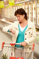 Stressed woman looking at her watch in the supermarket