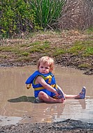 This cute 18 month old Caucasian toddler girl is sitting in her diaper and life vest in a mud puddle and playing as she´s taking off her sandal Great ...