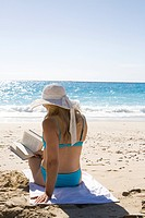 woman with hat reading at the beach