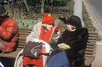 Two elderly ladies on a park bench talking, NY