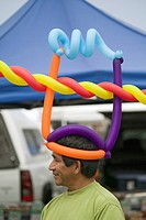 A Hispanic man wares multi_colored balloons on his head at farmers market in Santa Barbara California