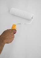 Hand and paint roller on a white wall