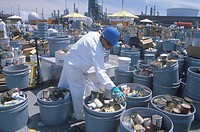 Worker sorting toxic wastes at waste cleanup site on Earth Day at the Unocal plant in Wilmington, Los Angeles, CA