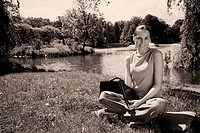 Woman with a leather file sitting in a park