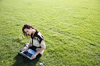 young woman sitting on grass while using laptop