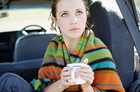 young woman sitting in the back of a jeep wrapped in blanket holding mug.