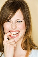 Young woman biting on finger and laughing