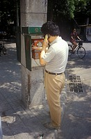 Chinese man making call at pay phone in Beijing in Hebei Province, People´s Republic of China