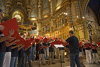 Boys & girls choir singing in the Benedictine Abbey at Montserrat, Santa Maria de Montserrat, near Barcelona, Catalonia, Spain with Black Madonna in b...