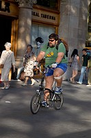 Overweight man riding bicycle on Passeig de Gràcia in the Eixample district, busy street in Barcelona, Spain, Europe