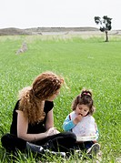 mother with baby girl having picnic in field