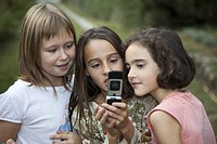 3 girls watching a sms in a cell phone