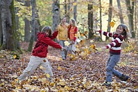 Brother and sister throwing leaves in autumn forest