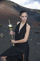 Young woman in black dress holding scepter in barren landscape