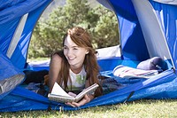 Young woman relaxing in tent with book, looking away