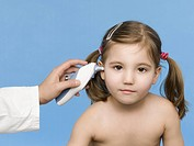 Young girl having temperature taken by doctor