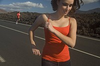 Young woman jogging along road with man in background