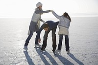 Father passing under arms of daughter and mother on ice