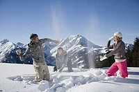 Three friends having snowball fight on ski slope, side view