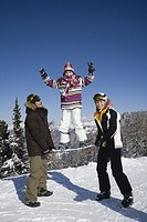 Portrait of mother and father holding daughter above snow on snowboard