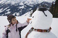 Young girl holding carrot nose of snowman