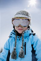 Portrait of young boy wearing ski goggles, smiling