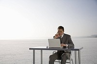 Mid adult business man using laptop on desk on ice