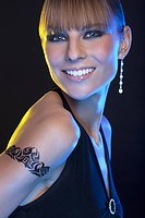 Portrait of young woman with tattoo, smiling