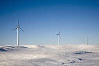 Windtowers in snowy field.