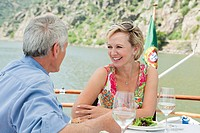 Senior couple having lunch on a boat holiday