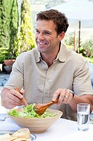 Mature man serving salad on holiday (thumbnail)