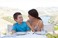 Mother and son sitting at table on holiday