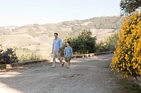 Father and son walking down rural lane on holiday