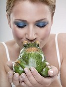 A portrait of a young woman kissing a frog