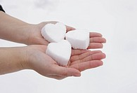 Hands holding heart shaped snowball
